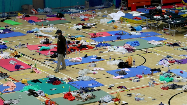 Une personne masquée marche dans un gymnase au plancher couvert de petits matelas, de vêtements et de babioles du quotidien.