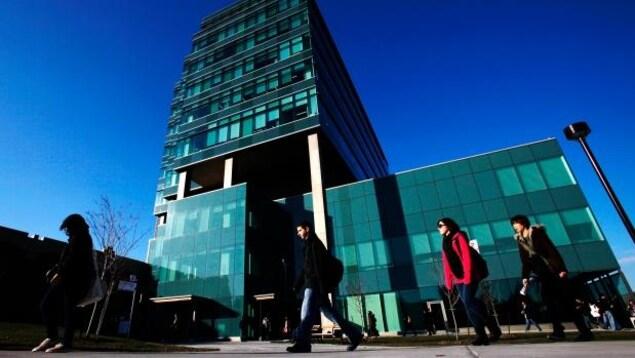 Des étudiants marchent devant un grand édifice en verre de l'université.