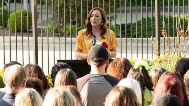 Une femme parle à un groupe de personnes.