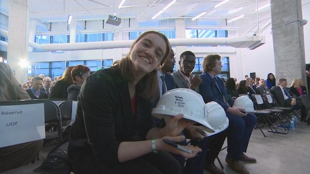 Une femme tient un casque de sécurité et sourit à la caméra.