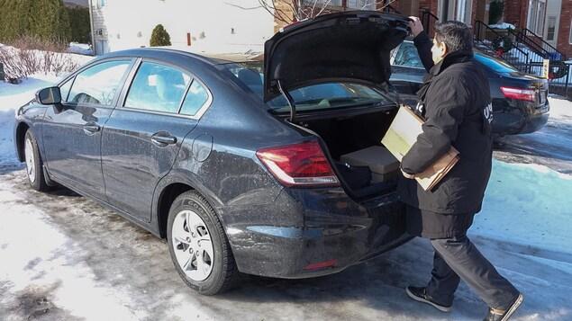 Un enquêteur de l'UPAC ayant saisi des documents les dépose dans le coffre de sa voiture.