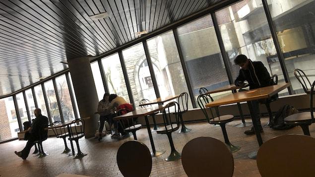 Des personnes assises à des tables dans un grand local vitré.