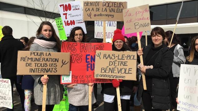 Quatre étudiantes tiennent des pancartes où des slogans sont inscrits. Il peut y lire «Pour la rémunération de tous les internats» et «La psycho est rendue un bingo»