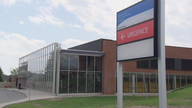 Un panneau portant la mention urgence et une flèche indiquant la porte d'entrée.