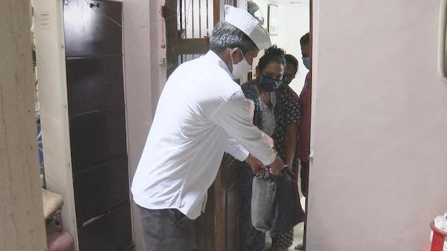 une femme tend un sac à un homme au pas de la porte.