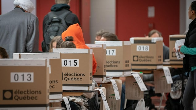 Un bureau de vote au Québec, où l'on voit plusieurs urnes.