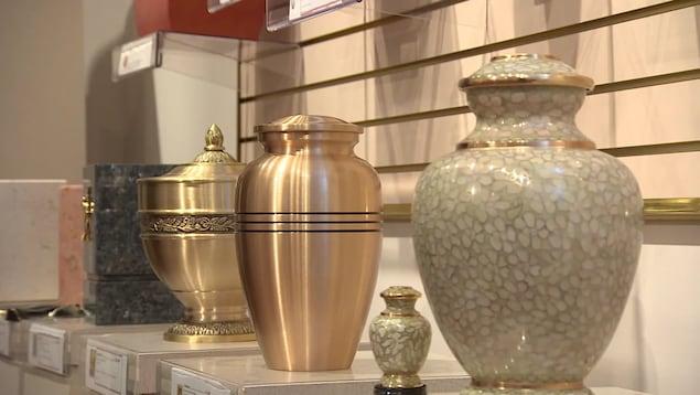 Plusieurs modèles d'urnes funéraires sur un étalage d'un salon funéraire.