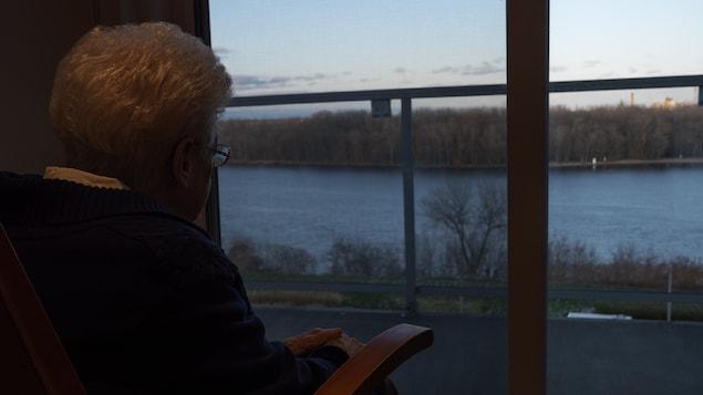 Soeur Louise-Hélène Albert regarde par la fenêtre de la nouvelle résidence, située au confluent de la rivière Saint-Maurice et du fleuve Saint-Laurent.
