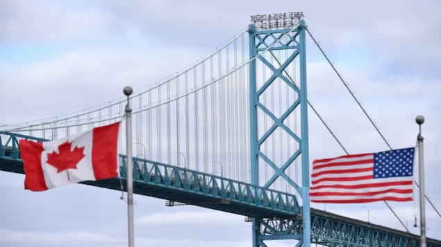 Canadian and American flags fly near the Ambassador Bridge at the border crossing in Windsor, Ont., on March 21, 2020, the first day the border closed to non-essential travel due to COVID-19