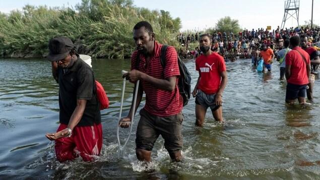 Une file de migrants traversant le Rio Grande.