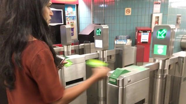 Photo d'une femme aux cheveux noirs, portant un t-shirt brun, qui tient une carte verte dans la main devant une borne du métro.
