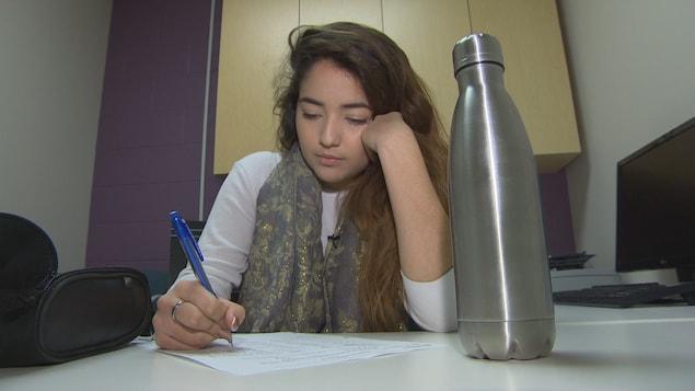 Une jeune femme assise à une table avec en avant-plan sa bouteille d'eau. Elle regarde une feuille sur son plan de travail, elle tient un crayon de la main droite et appuie sa tête sur sa main gauche.