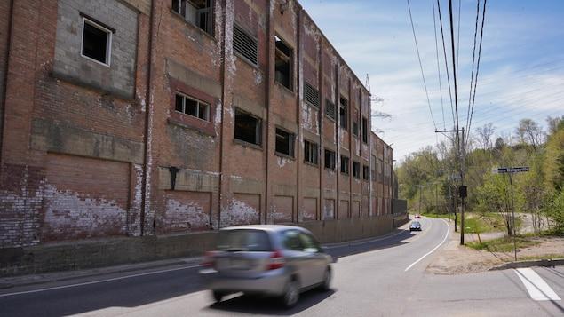 Une usine désaffectée en bordure d'une route.