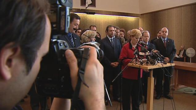 Entourée d'acteurs politiques, Lise Landry prend la parole lors d'une conférence de presse.