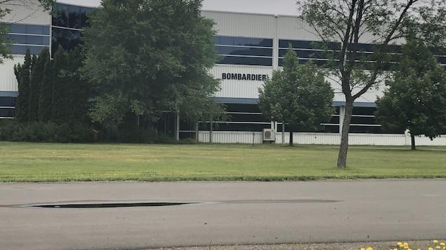 Un bâtiment industriel en partie caché par des arbres.