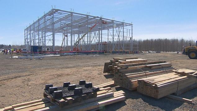 Un immeuble en pleine construction avec des planches de bois en hiver.