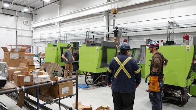 Des travailleurs portant des casques de sécurité dans une usine avec des boîtes en carton et des machines vertes.