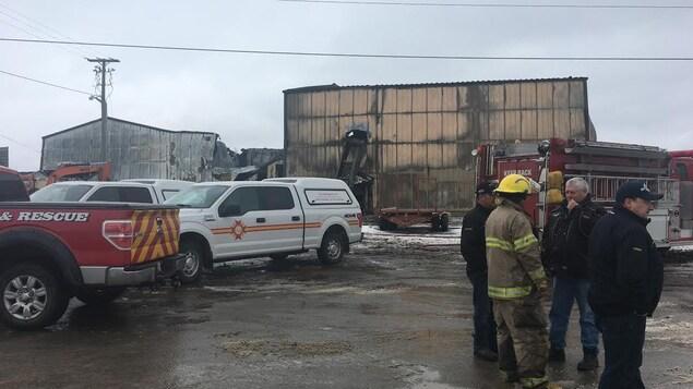 Des véhicules d'urgence et des pompiers devant les ruines de l'usine