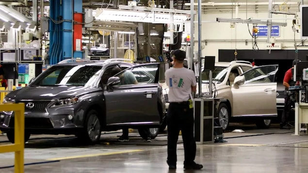 Une ligne d'assemblage avec trois hommes et deux voitures.
