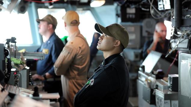 Des hommes travaillent à bord d'un navire.