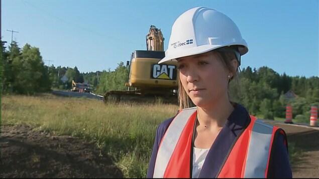 Une dame porte un casque blanc et un dossard sur les lieux d'un chantier de construction.