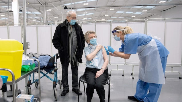 Une infirmière vaccine une femme âgée, sous le regard de son mari.