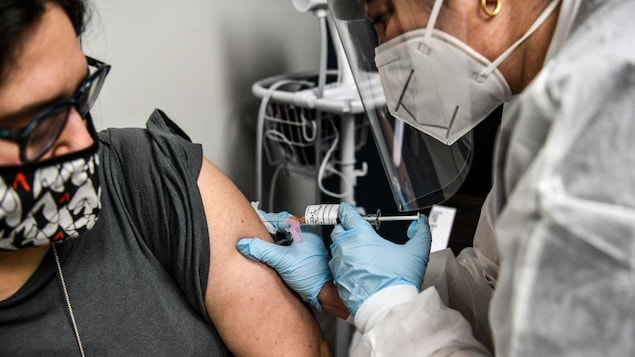 Une travailleuse de la santé administre un vaccin contre la COVID-19 lors d'essais cliniques à une femme qui porte un couvre-visage.