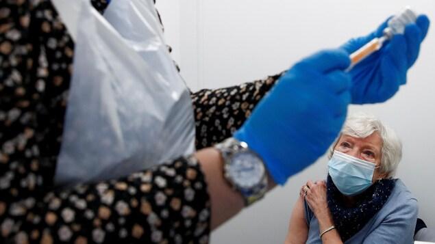 Doreen Vickers, 83 ans, s'apprête à recevoir le vaccin d'Oxford-AstraZeneca contre la COVID-19, le 14 janvier 2021 à Widnes, en Grande-Bretagne.