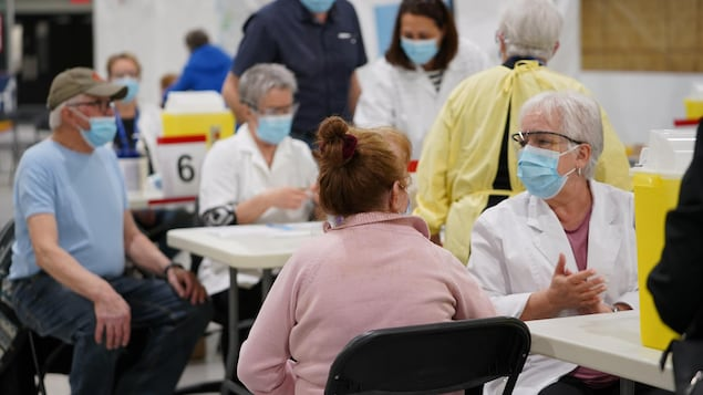 Des employés avec masque et lunettes qui s'apprêtent à vacciner des citoyens à Louiseville.