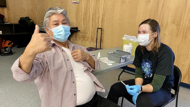 Un homme a un pouce en l'air après avoir reçu son vaccin.