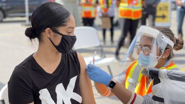 Une jeune femme se fait injecter le vaccin dans l'épaule.