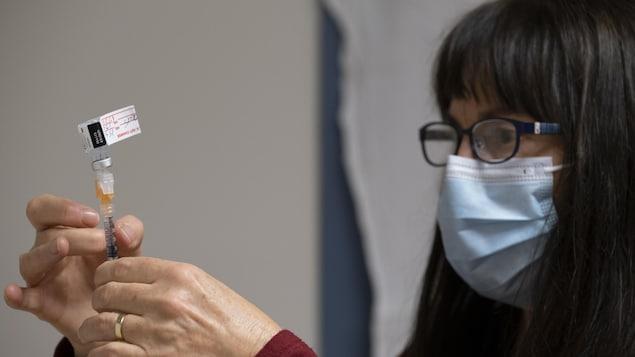 Une infirmière clinicienne prépare un vaccin contre la COVID-19.