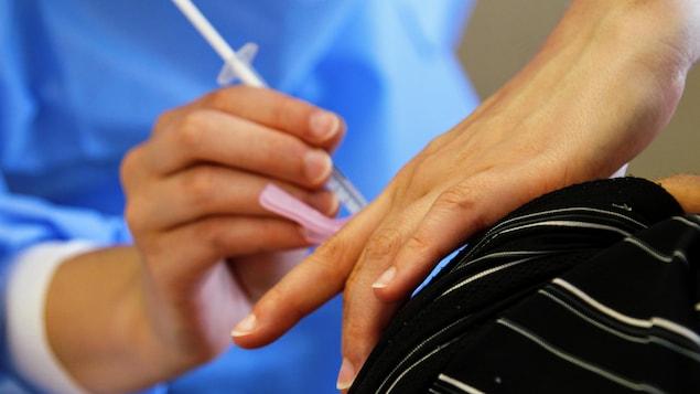 Une infirmière injecte un vaccin contre la COVID-19 dans le bras d'un homme.