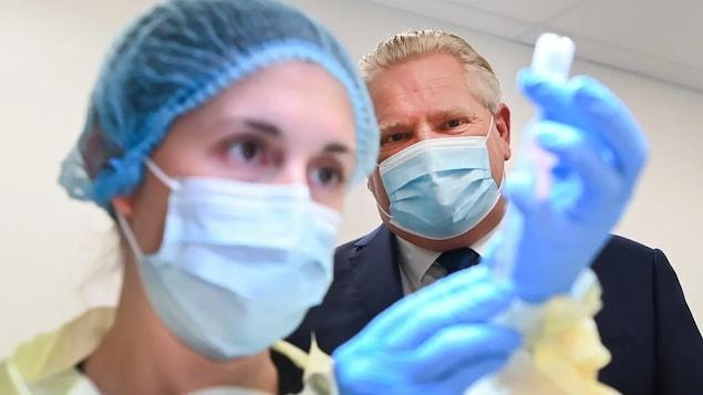 Le premier ministre de l'Ontario, Doug Ford, observe une infirmière préparer une dose du vaccin contre la COVID-19.