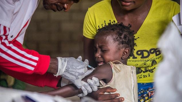 Un enfant assis sur les genoux de sa mère se fait vacciner.