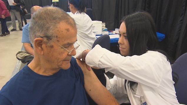 Une infirmière administre à un homme un vaccin contre le grippe.