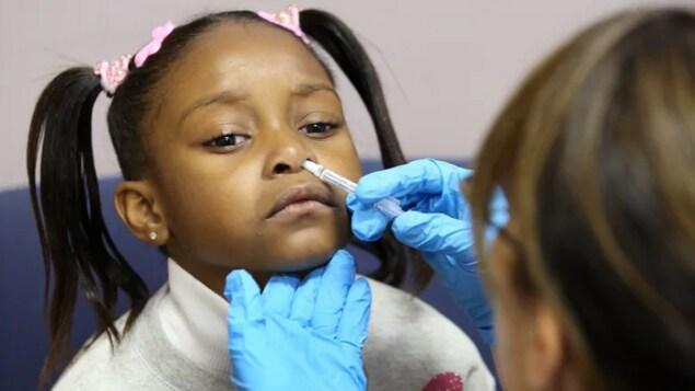 Une petite fille reçoit un vaccin par vaporisateur nasal.