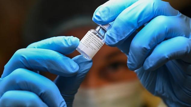 Une personne manipule un fiole de vaccin.
