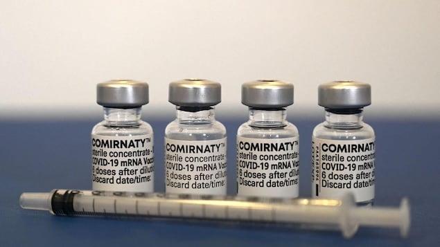 Quatre fioles contenant des doses du vaccin de Pfizer-BioNTech contre la COVID-19, alignées derrière une seringue.