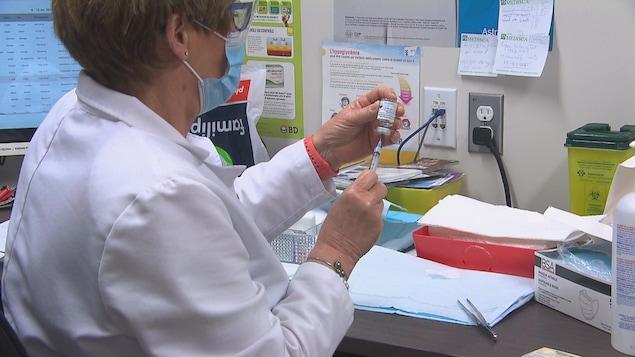 Une infirmière prépare un vaccin dans un bureau.