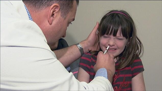 Une fille reçoit un vaccin pour la grippe dans une narine.