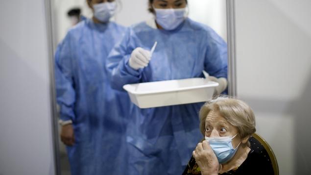 Une dame âgée s'apprêtant à se faire vacciner.