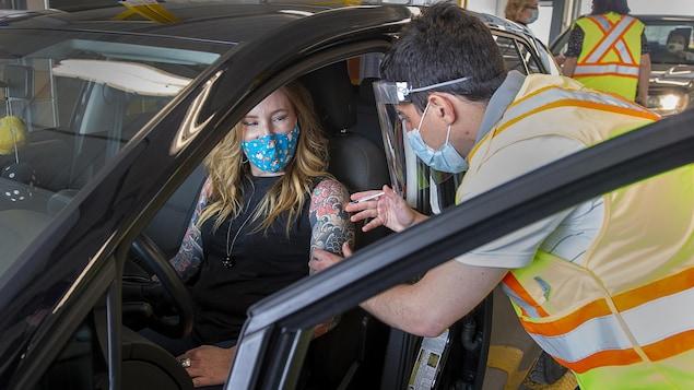 Une femme assise au volant de sa voiture se fait vacciner par un infirmier.