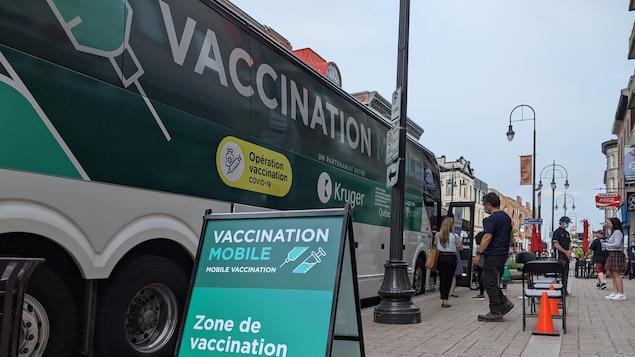Des gens font la file devant l'autocar qui fait office de clinique mobile de vaccination.