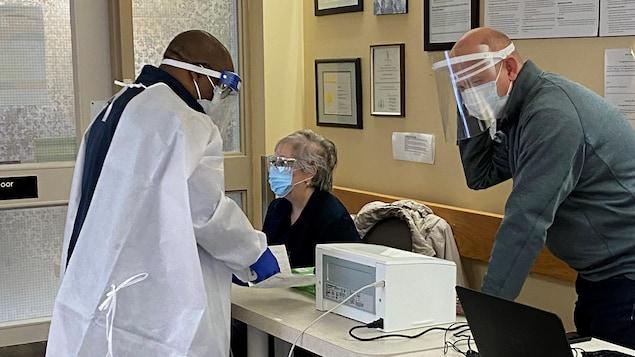 Trois personnes portant le masque près d'ordinateurs.