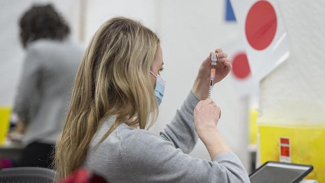 Une femme de profil qui prépare une dose de vaccin.