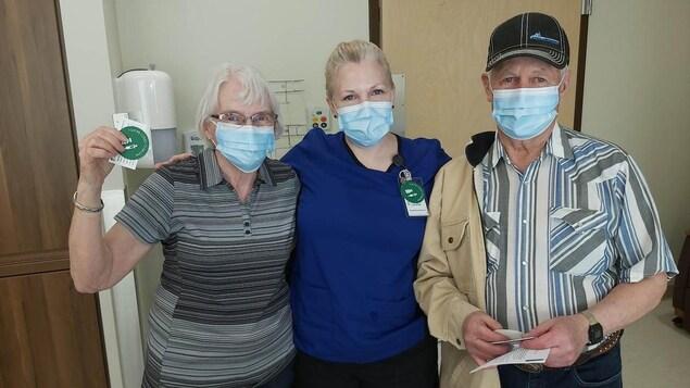 Une infirmière en compagnie de ses parents dans un centre de vaccination.