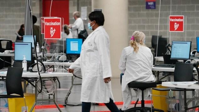 Des préposés au centre de vaccination du stade olympique de Montréal.