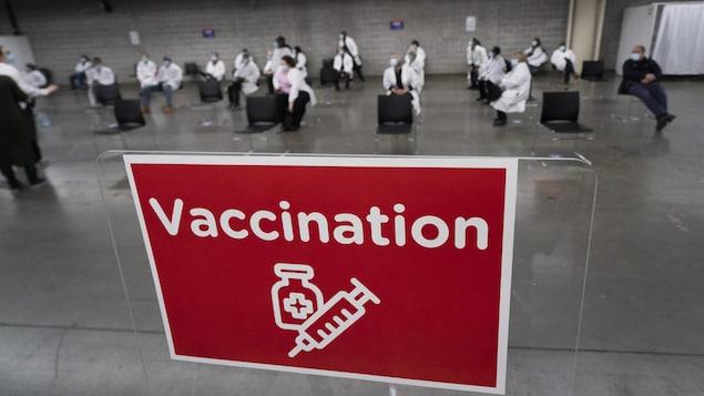 Une affiche rouge sur laquelle est écrit vaccination avec, en arrière-plan, des préposés vêtus en blanc.