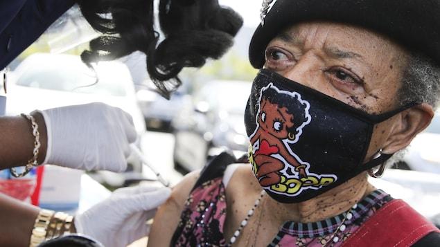 La dame, qui porte un masque avec une image de Betty Boop, reçoit son vaccin sur l'épaule.